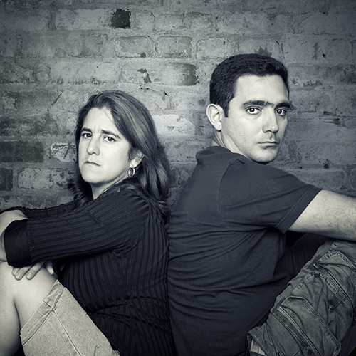 Couple with autism sitting back-to-back with serious and somewhat angry expressions