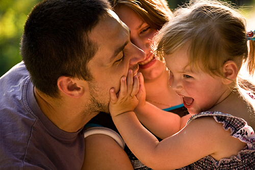 Playful mother, father and daughter with autism spectrum disorder or other neurodevelopmental challenge
