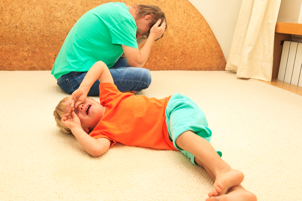 Boy with autism spectrum disorder or other neurodevelopmental challenge, laying on the floor crying, frustrated father with hands on his head