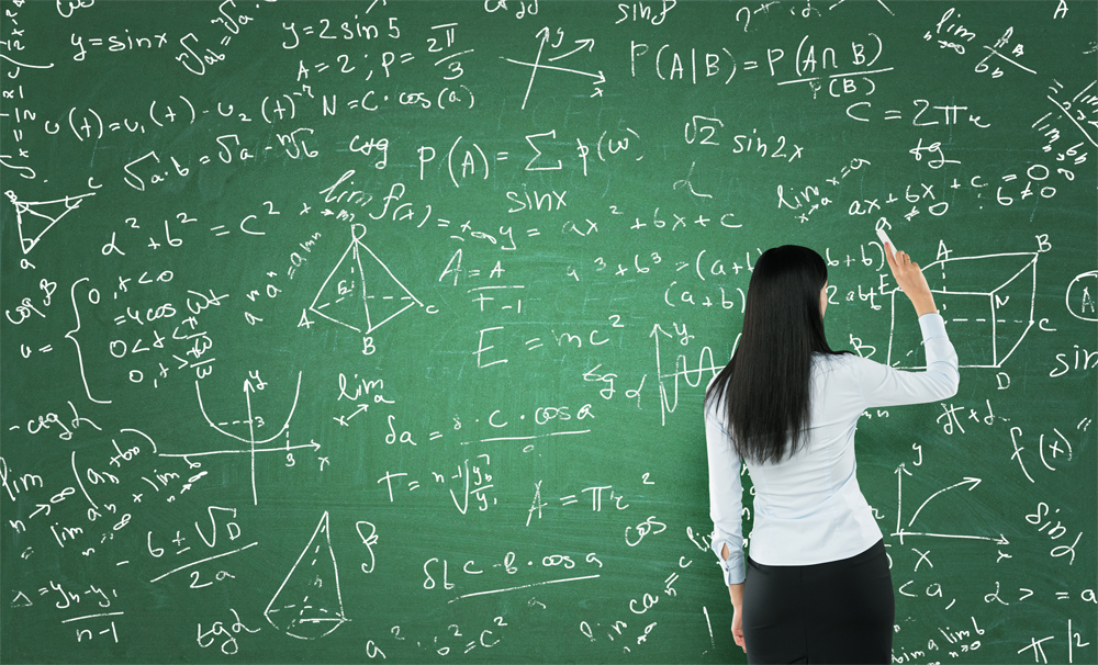 Woman diagnosed with autism spectrum disorder writing on a chalk board full on math equations