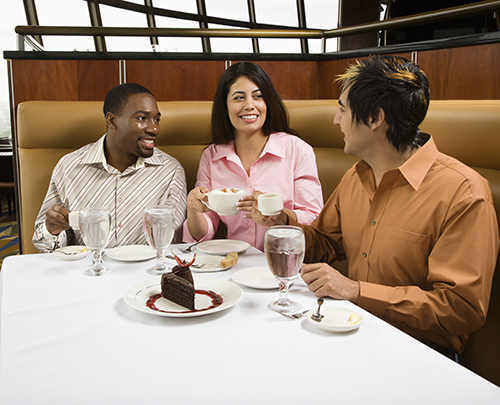 Two men and a woman sitting in a booth at a restaurant talking and smiling, at least one person is diagnosed with autism spectrum disorder
