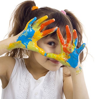 Playful girl with ADHD (Attention Deficit Hyperactivity Disorder) with paint all over her hands