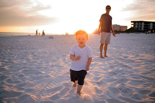 Young boy ADHD (Attention Deficit Hyperactivity Disorder) running from his father on the beach