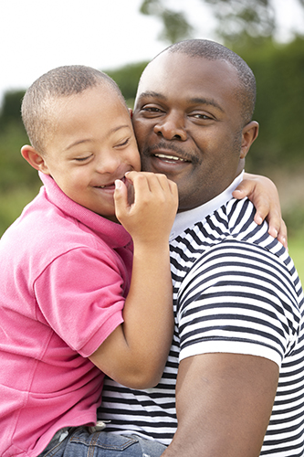 Father holding his son with Down syndrome, both are smiling