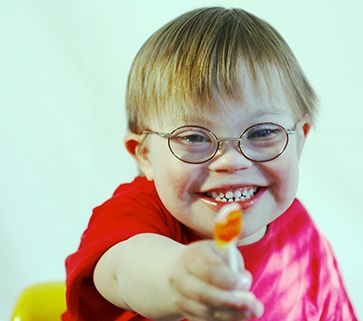 Smiling boy with Down syndrome, handing a sucker toward the viewer