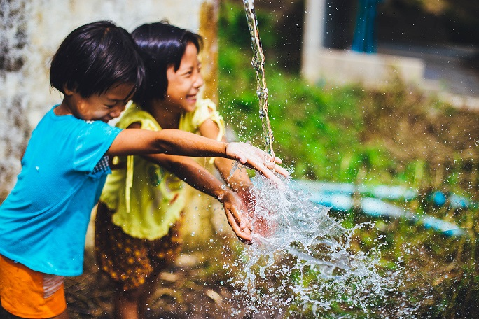 Two brothers giggling and playing in a stream of water