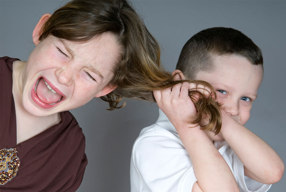 Brother with autism, smirking, pulling his sisters hair, and she looks upset and in pain