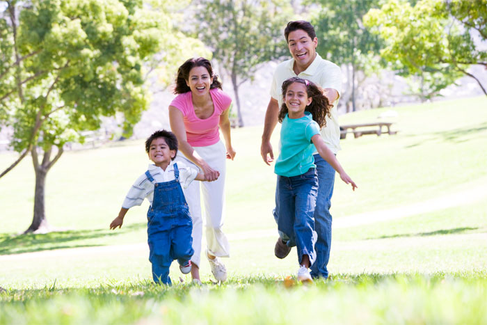 Family - mother holding sons hand and father holding daughters hand, running and smiling