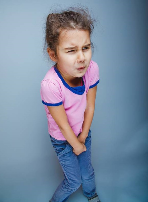 Young girl on the autism spectrum with hands between her legs and tense expression, needing to go to the toilet