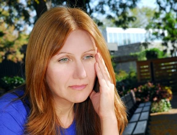 Adult woman with autism looking serious with her hand on the side of her face