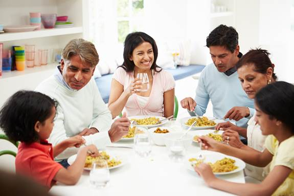 Family, parents, grandparents and 2 children sitting at the dinner table, eating, talking and smiling