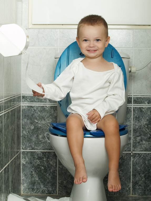 Young boy sitting on the toilet, smiling and pulling on the toilet paper