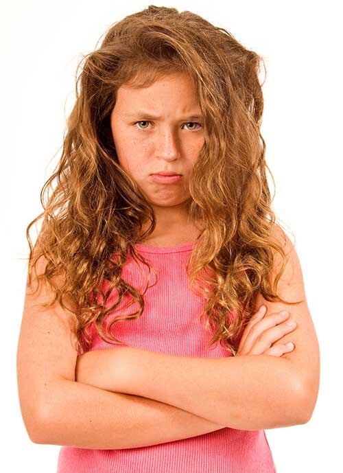 Young girl with autism spectrum disorder or other neurodevelopmental challenge with arms folded, pouting, appearing defiant