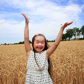 Smiling girl with Down syndrome in a field with her arms in the air