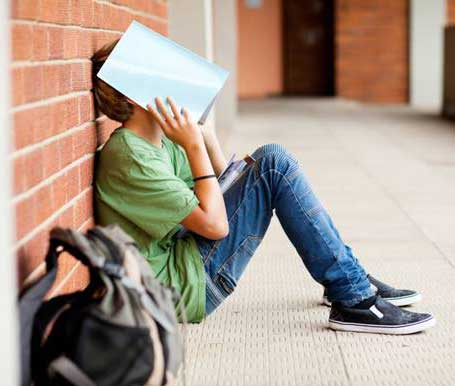 Teen with autism spectrum disorder sitting against a brick wall at school with notebook over his face and head