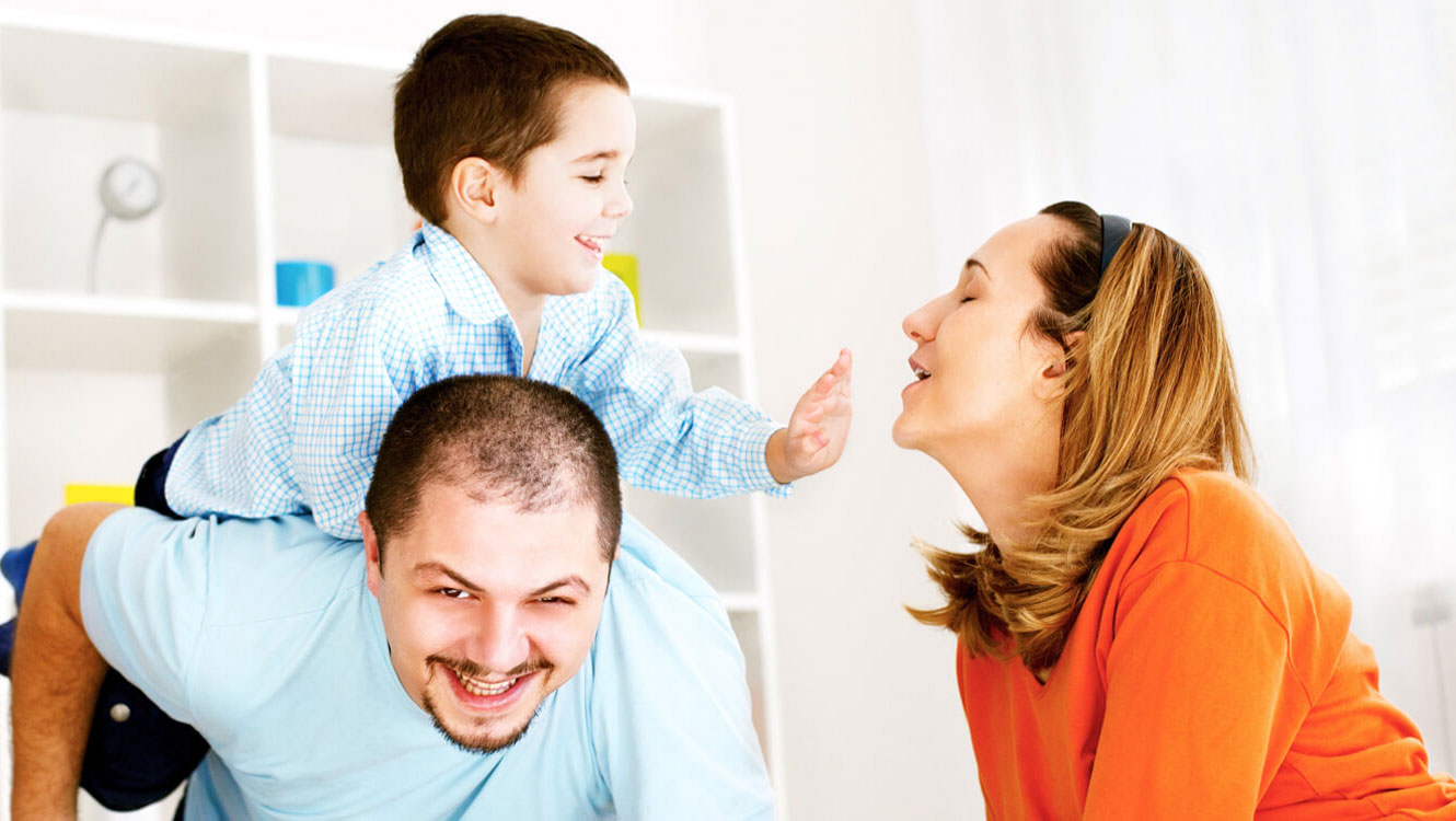 Family – mother and father playing with son who has autism spectrum disorder
