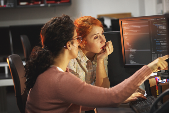 Women on the autism spectrum, working on a computer with multiple screens